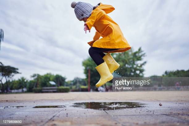 mid-air shot of a child jumping in a puddle of water wearing yellow rubber boots and a raincoat in autumn - jumping stock pictures, royalty-free photos & images
