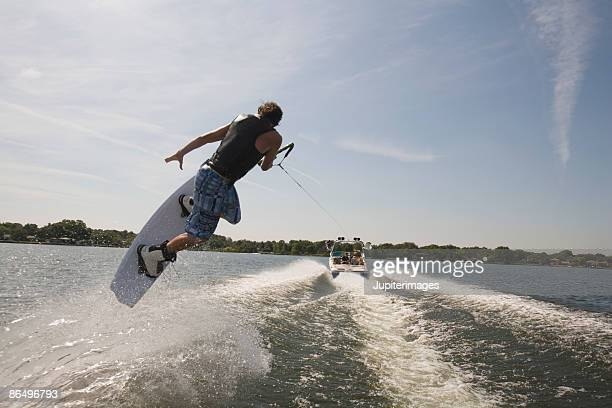 midair wakeboarder and boat - waterskiing stock photos and pictures