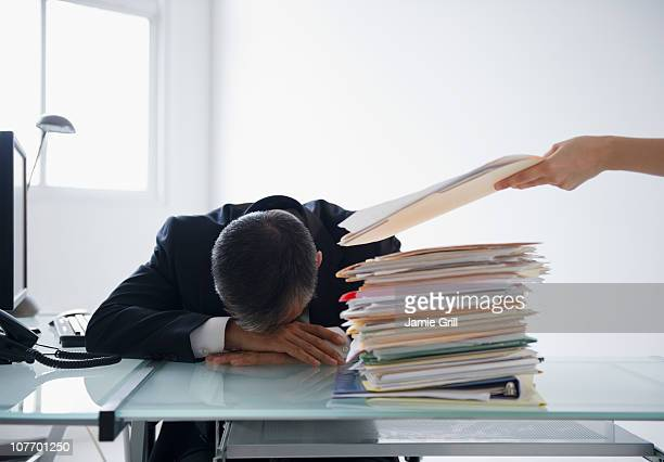 usa, mid-atlantic usa, new jersey, businessman with head on desk and pile of documents in front of him - overworked stock pictures, royalty-free photos & images