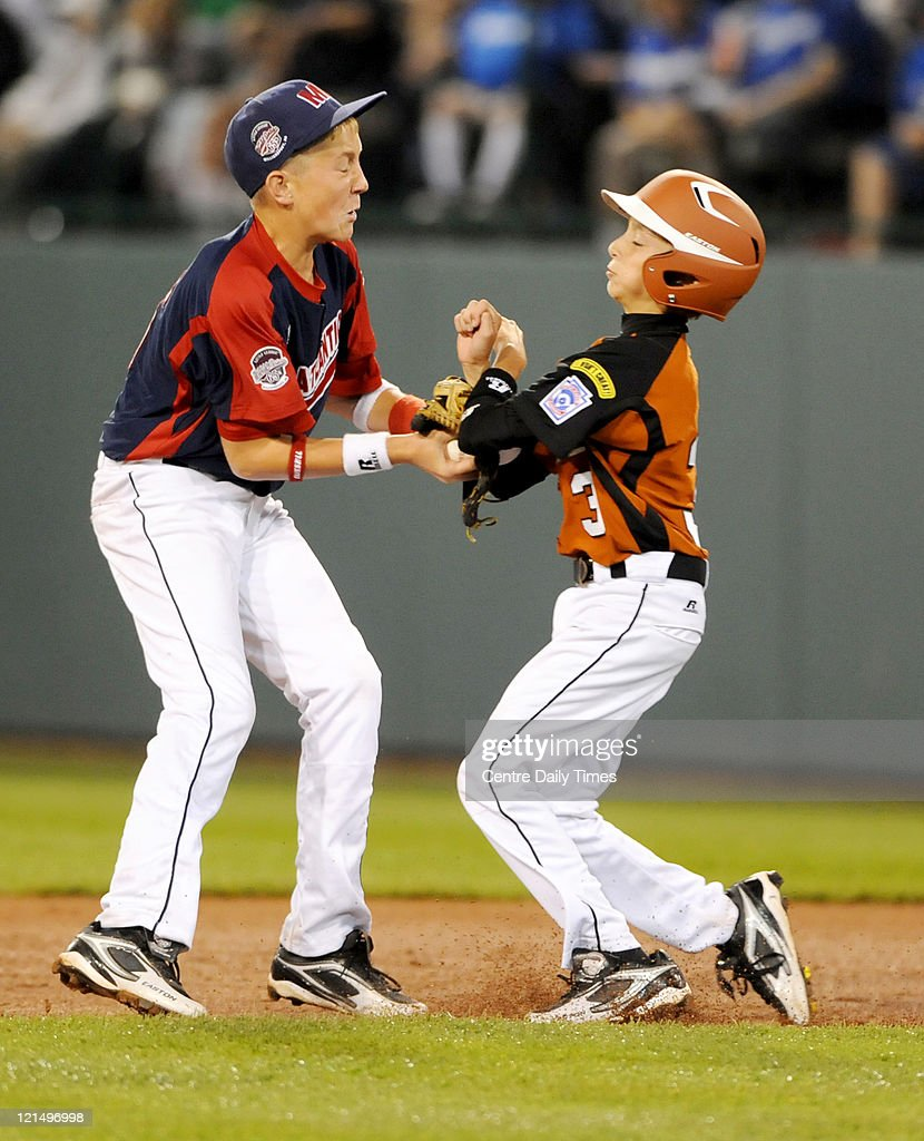 Mid-Atlantic's Alex Garbrick, left, tags out Great Lakes' Nick McKinney as he runs towards second base at Lamade Stadium in South Williamsport, Pennsylvania, in the 2011 Little League World Series on Friday, August 19, 2011.