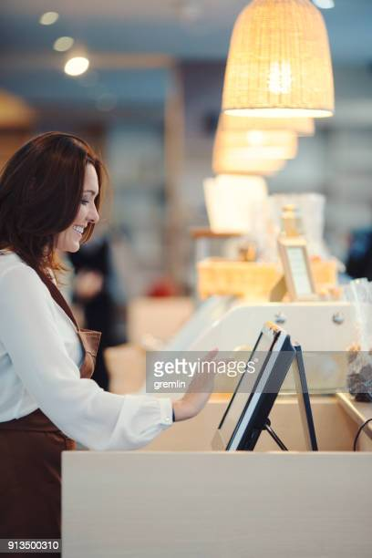 middle age barista typing on cash register - register stock photos and pictures