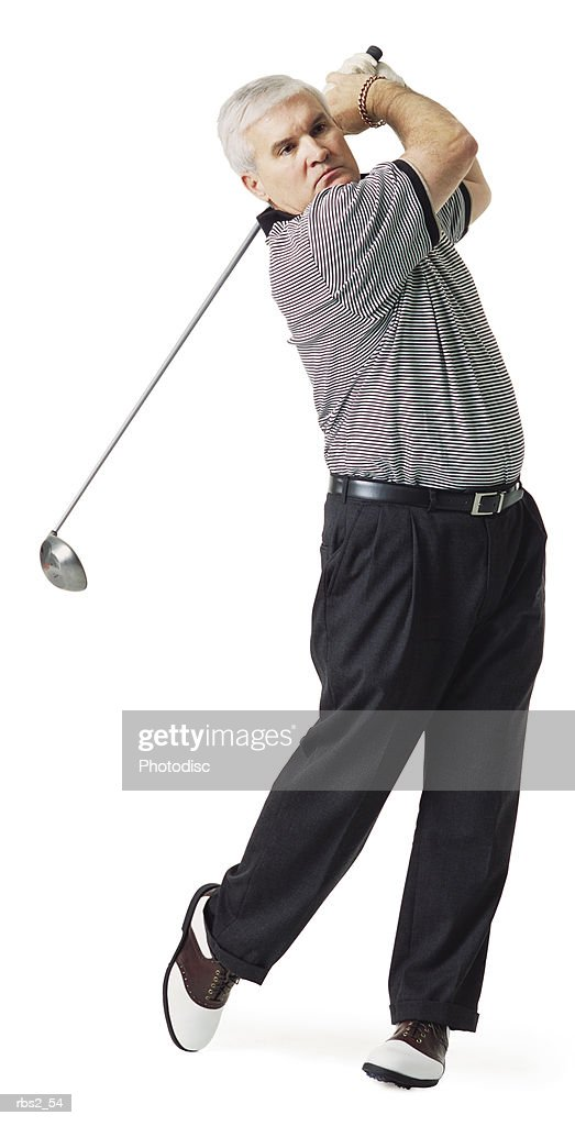 middle age caucasian man wears gray golf shirt saddle shoes swings golf club after hitting the ball : Foto de stock