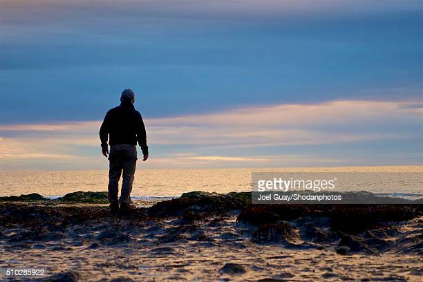 middle age man standing on rocks against surf background