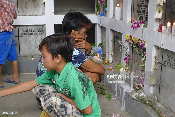 A middle age woman and a boy religiously praying at their relative's niches