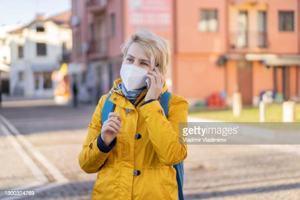 middle age woman answering her mobile phone on the street - department of health and human services stock pictures, royalty-free photos & images