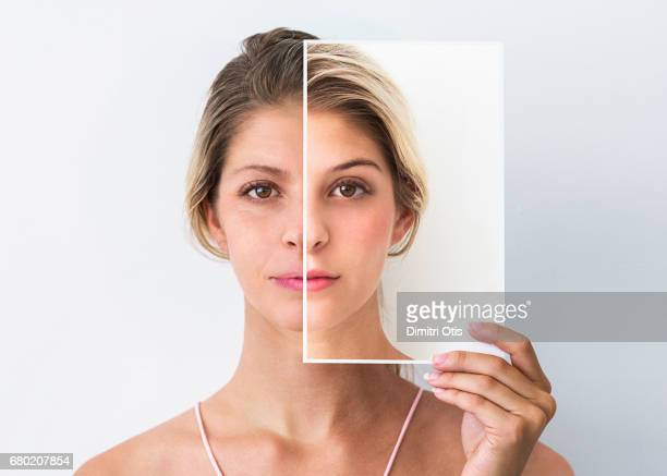 middle age woman holding photo of face when she was younger - faltenreduktion stock-fotos und bilder