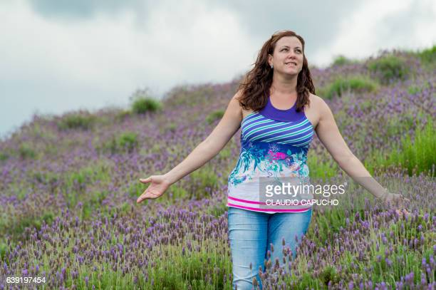 a middle age woman in lavender field - claudio capucho stock photos and pictures