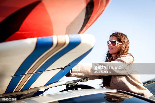 middle age woman prepares to paddle board