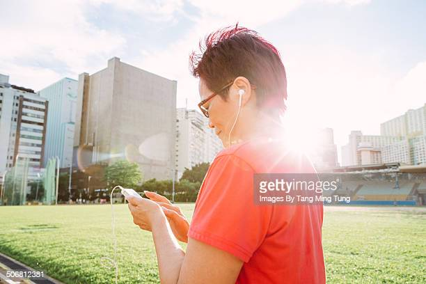Middle age woman using smartphone in sports ground