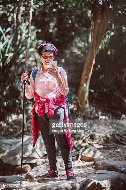 Middle age woman using smartphone while hiking