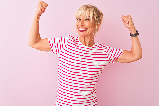 Middle age woman wearing striped t-shirt standing over isolated pink background showing arms muscles smiling proud. Fitness concept. 1173773407