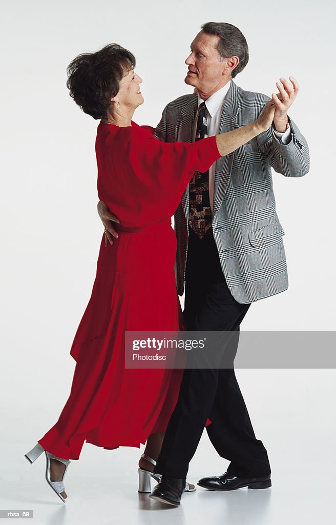 middle aged adult caucasian brunette female wearing a long red dress and middle aged adult caucasian gray haired male wearing a suit and tie holding each other in a dance pose as they look into each others eyes smiling : Foto de stock