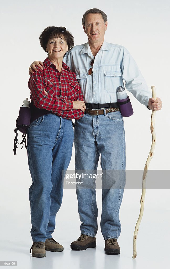 middle aged adult caucasian female wearing jeans and a red flannel shirt with a water bottle standing with middle aged adult caucasian male wearing jeans and a blue shirt and water bottle holding hiking stick and looking at the camera smiling as a co : Foto de stock