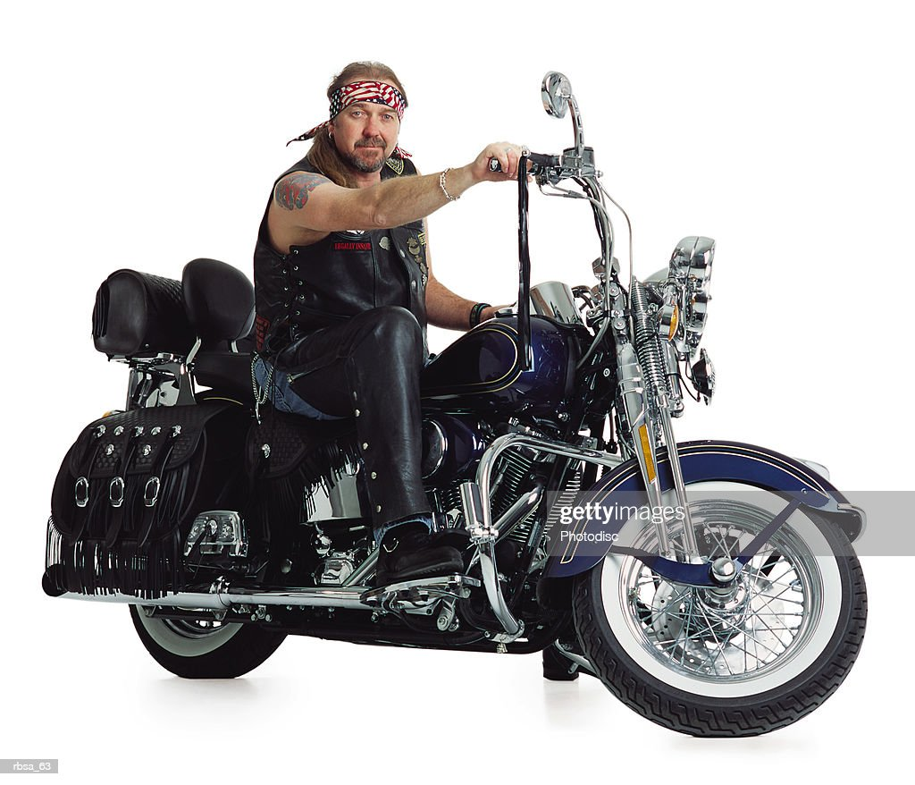 middle aged adult caucasian male sits on motorcycle smiles slightly at the camera : Stock Photo
