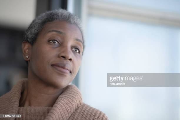 middle aged african woman reflecting stock photo - 40 49 years stock pictures, royalty-free photos & images