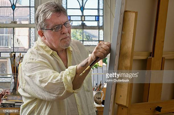 Middle aged artist working the canvas