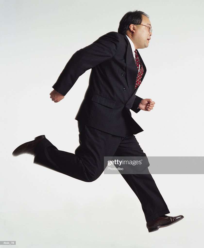 middle aged asian businessman with glasses wears a dark business suit running sideways to the camera : Foto de stock
