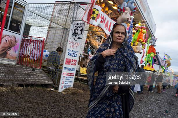 Middle aged Asian woman, dressed in traditional style sari walks amongst the stalls at The Hoppings fun fair, Newcastle upon Tyne. Her hand is raised...