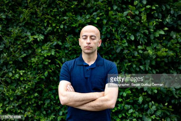 a middle aged bald man with his eyes closed and arms crossed - thinking outside the box englische redewendung stock-fotos und bilder