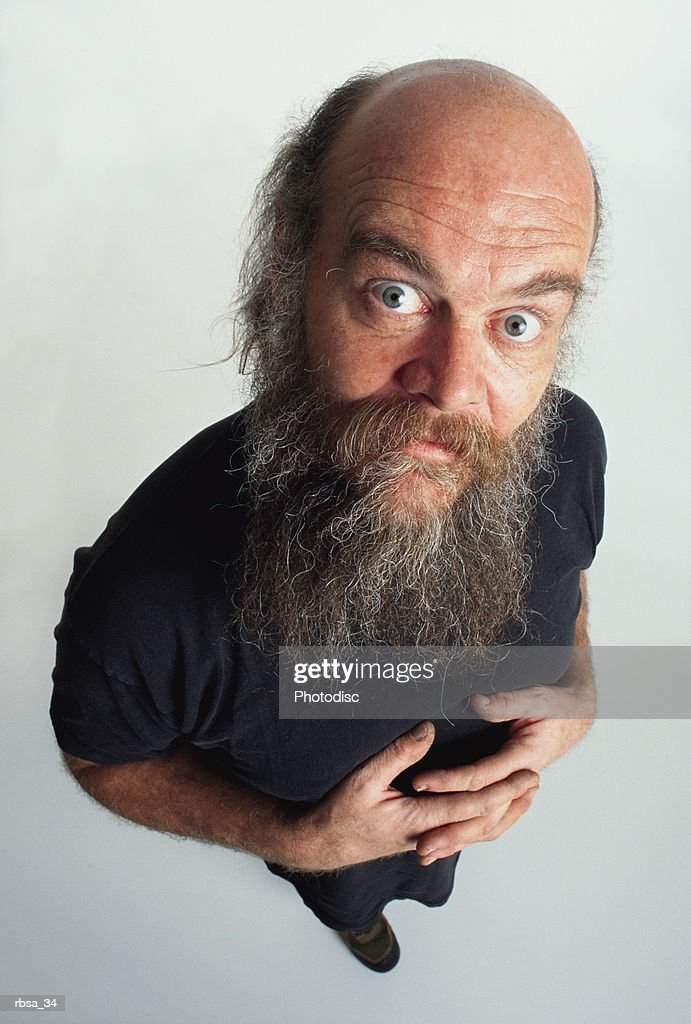 middle aged balding caucasian male adult with facial hair wears a dark t-shirt and looks up at the camera with wide eyes and an anxious expression : Foto de stock