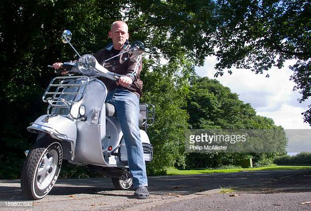 Middle aged balding man straddles a Vespa PX125.He is looking directly into the camera which is at a low viewpoint.