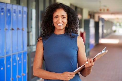 Middle aged black female teacher smiling in school corridor 826213524