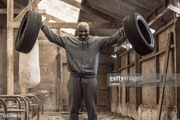 middle aged black fighter working out in an abandoned farm - masculinity stock pictures, royalty-free photos & images