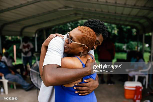 middle aged black mother hugging her son - embracing stock pictures, royalty-free photos & images