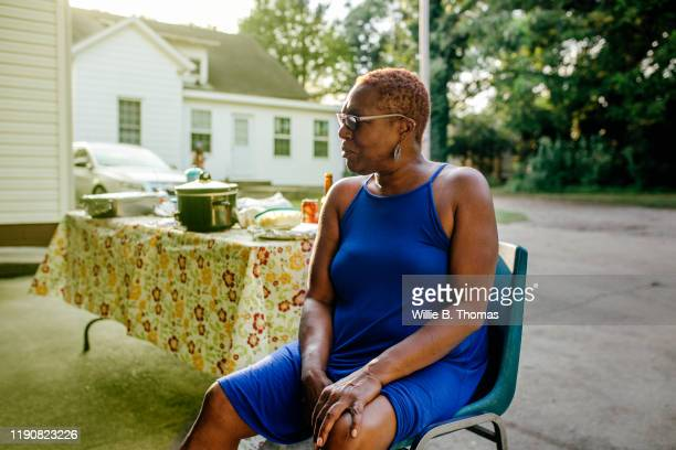 middle aged black woman sitting outdoors - hand on knee stock pictures, royalty-free photos & images