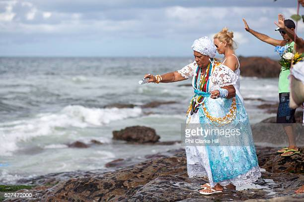 Middle aged Brazilian woman Bahiana in traditional Candomble dress of white praying and making offerings of flowers to the sea in honour of Yemanja...
