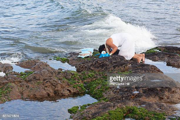 Middle aged Brazilian woman in traditional Candomble dress of white praying and making offerings of flowers to the sea in honour of Yemanja February...