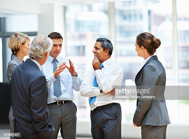 Middle aged business man having a discussion with his team