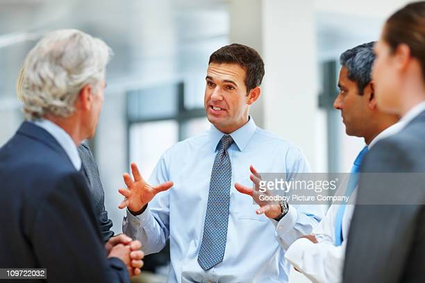 Middle aged business man having discussion with his team