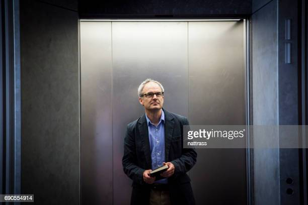 middle aged business man on an elevator - one man only stock pictures, royalty-free photos & images