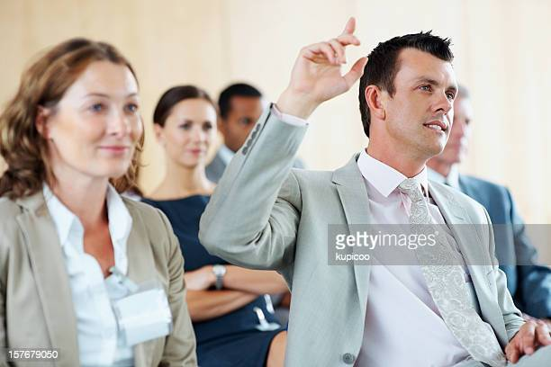 middle aged business man raising hand to ask question - master's degree stock pictures, royalty-free photos & images
