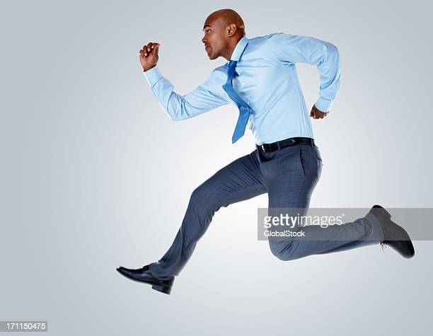 Middle aged business man running against colored background