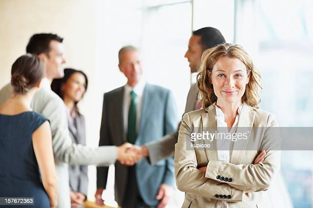 Middle aged business woman with hands folded and blur team