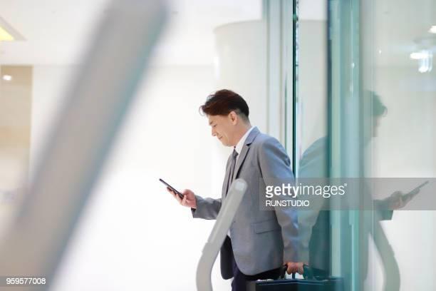 middle aged businessman coming out of the elevator - eingangshalle gebäudeteil stock-fotos und bilder