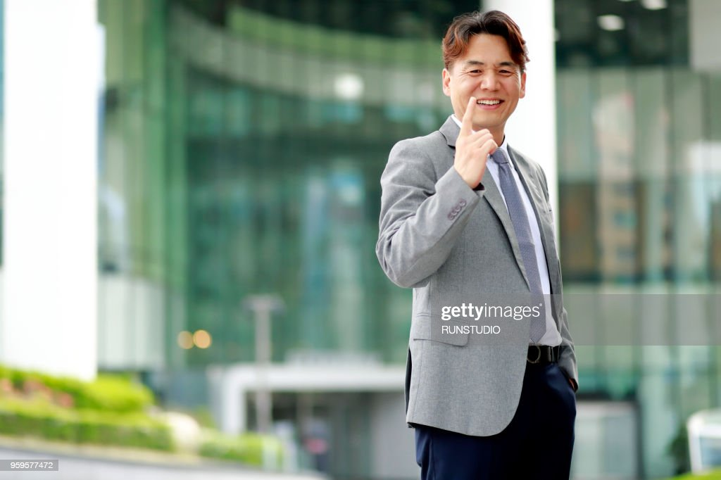 Middle aged businessman pointing finger outdoors : Stock-Foto
