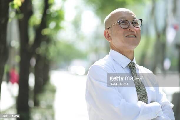 middle aged businessman standing with arms folded outside office building - koreanischer abstammung stock-fotos und bilder
