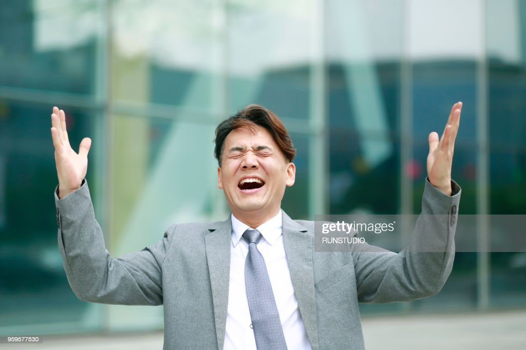 Middle aged businessman standing with arms raised outdoors : Stock-Foto
