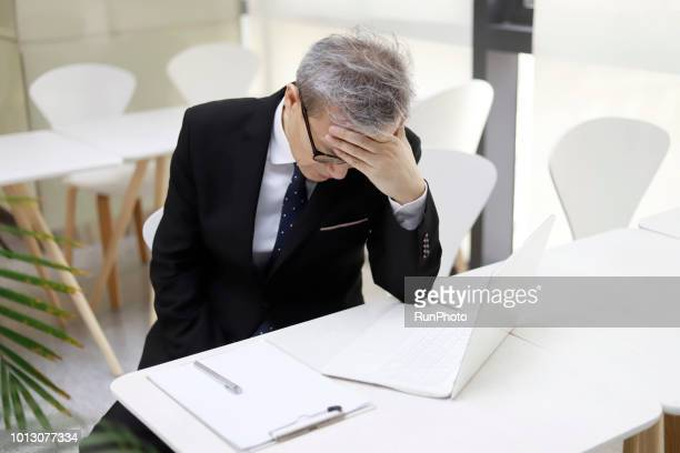 middle aged businessman suffering from headache - 中年の男性一人 ストックフォトと画像