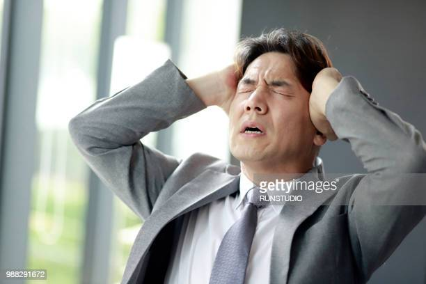 middle aged businessman suffering from headache - 問題 ストックフォトと画像