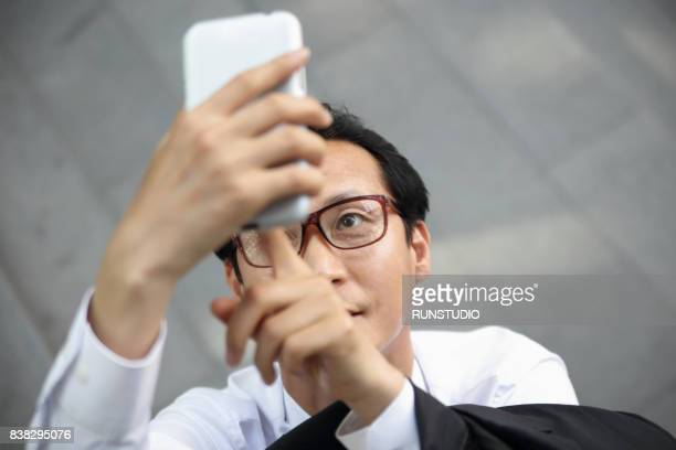 middle aged businessman using smartphone outdoors