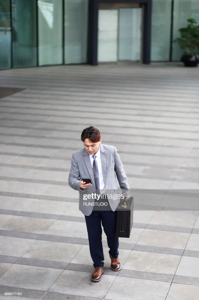 Middle aged businessman using smartphone  outside office building : Stock-Foto