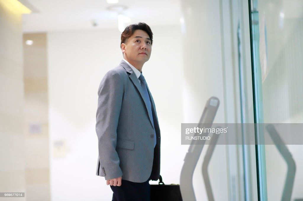 Middle aged businessman waiting for elevator in office corridor : Stock-Foto