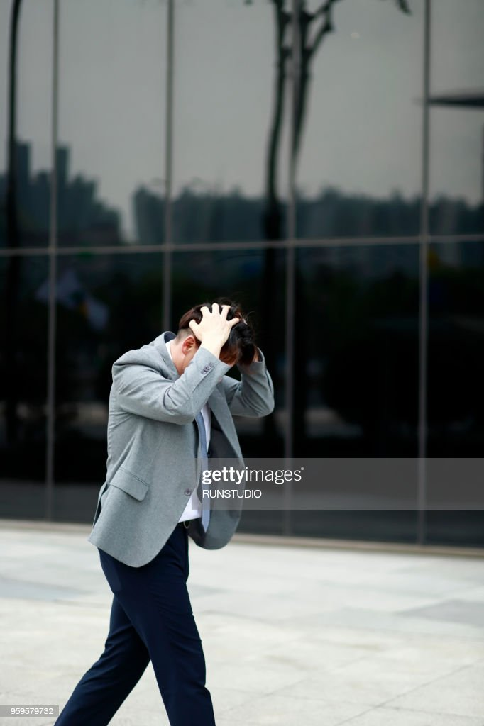 Middle aged businessman walking with hands on head outdoors : Stock-Foto