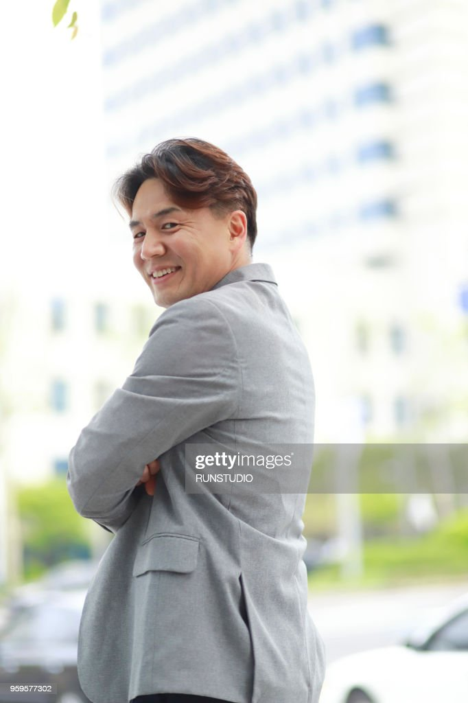Middle aged businessman with arms folded outside office building : Stock-Foto