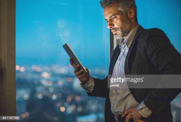 Middle aged businessman with digital tablet at night