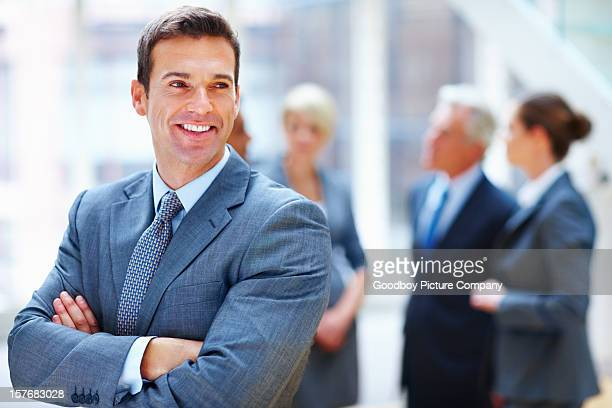 Middle aged businessman with hands folded and team in background